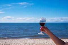Un verre de vin rouge dans une main du ` s de femme avec une belle manucure Contre le contexte d'une plage ensoleillée Mer bleue  Photos stock