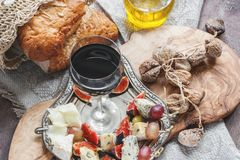Un verre de vin rouge sec et pain italien de focacce avec l'huile de fromage et d'olive et les tomates séchées au soleil Foyer sé Photographie stock