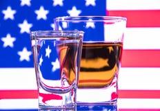 Un verre de vodka et un verre d'eau-de-vie fine, de whiskey ou de bourbon sur un blanc ou un fond coloré Images stock