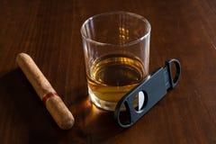 Un verre de whiskey avec le cigare et le coupeur de cigare Images libres de droits