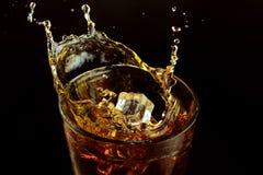Un verre de whiskey sur un fond foncé Glaçon d'éclaboussure photos stock