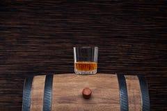 Un verre de whiskey sur un vieux baril de chêne photographie stock libre de droits
