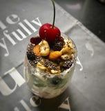Un verre de yaourt, avec la cerise, le sésame, la noix, les fruits secs, le kiw et la crème Images libres de droits