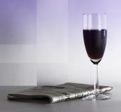 Un verre du vin rouge et d'un journal Photographie stock libre de droits