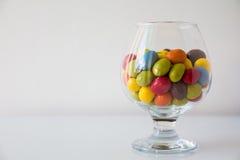 Un verre plein des pastilles de chocolat colorées Photos stock