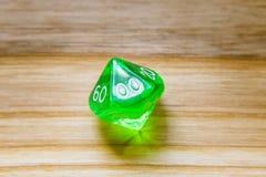 Un vert translucide dix a dégrossi jouant des matrices sur un backgroun en bois Image libre de droits