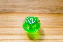 Un vert translucide douze a dégrossi jouant des matrices sur un backgr en bois photos stock