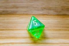 Un vert translucide huit a dégrossi jouant des matrices sur un backgro en bois photographie stock libre de droits