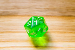 Un vert translucide vingt a dégrossi jouant des matrices sur un backgr en bois photos stock
