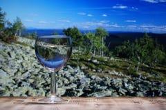 Un vetro vetro/vetro con acqua pulita sta su una tavola di legno contro un paesaggio della montagna Fotografie Stock