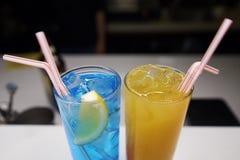 Un vetro con un cocktail blu e giallo con ghiaccio sul contatore della barra Immagini Stock Libere da Diritti