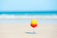 Un vetro con la bevanda sulla spiaggia dal mare Immagine Stock Libera da Diritti
