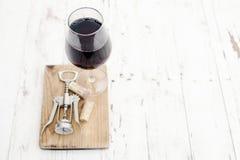 Un vetro dei sugheri del vino rosso, della cavaturaccioli e del vino su bianco rustico Immagini Stock Libere da Diritti
