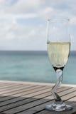 Un vetro del champagne dall'oceano fotografia stock libera da diritti