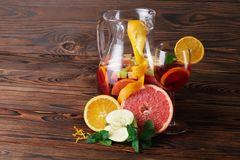 Un vetro del cocktail con le fragole e menta ed arancio, mela e pompelmo su un fondo marrone di legno Fotografia Stock