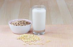 Un vetro del latte di soia con una ciotola di soia cruda Fotografie Stock