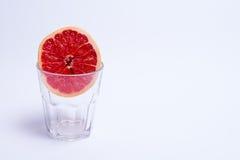 Un vetro del pompelmo rosa su fondo bianco Fotografia Stock