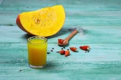 Un vetro del succo della zucca disposto su una tavola vicino alle zucche Il nuovo raccolto delle zucche Succo della zucca sulla t immagini stock libere da diritti
