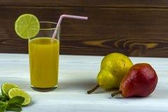 Un vetro del succo di arancia di recente compresso Ramoscelli della menta e fette di calce e di due pere fotografie stock libere da diritti