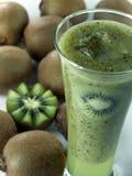 Un vetro del succo del kiwi con le fette ed i frutti Fotografia Stock