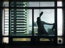 Un vetro dell'edificio per uffici di pulizia dell'uomo Fotografia Stock