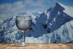 Un vetro di acqua pulita sta su una tavola di legno contro il paesaggio della montagna dell'inverno Immagine Stock Libera da Diritti