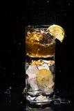 Un vetro di alta qualità di whiskey con spruzza la condizione su un altro Fotografia Stock