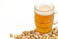 Un vetro di birra e dei pistacchi su fondo bianco fotografia stock libera da diritti