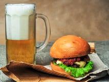 Un vetro di birra e di un cheeseburger su una carta del mestiere Fotografia Stock