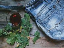 un vetro di brandy, le foglie della quercia, le ghiande e un denim insaccano sui bordi di legno Immagine Stock