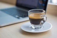 Un vetro di caffè e del computer portatile sulla tavola Immagini Stock