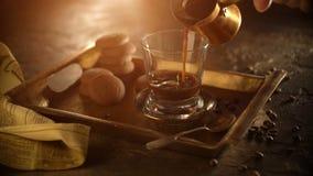 Un vetro di caffè nero pieno di vapore caldo su un vassoio del metallo, stante su una tavola di legno, circondata dai chicchi di  stock footage