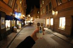 Un vetro di carta di caffè in una mano del ` s dell'uomo in una via Stoccolma di notte fotografia stock