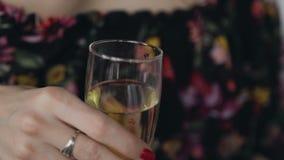 Un vetro di champagne nella mano della giovane donna La ragazza tiene un vetro di vino bianco in sue mani Vetro di champagne dent archivi video