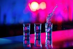 Un vetro di colpo di vodka con ghiaccio sulla barra, su un fondo rosso Fotografia Stock