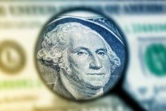 Un vetro di ingrandimento della banconota in dollari Fotografie Stock Libere da Diritti