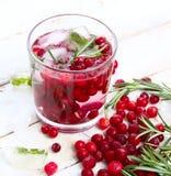 Un vetro di limonata ghiacciata dal mirtillo rosso, dai mirtilli rossi e dai rosmarini su un fondo di legno bianco Fotografia Stock Libera da Diritti