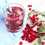 Un vetro di limonata ghiacciata dal mirtillo rosso, dai mirtilli rossi e dai rosmarini su un fondo di legno bianco Immagine Stock Libera da Diritti