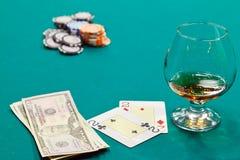 Un vetro di liquore e schede e dollari Fotografie Stock