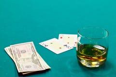 Un vetro di liquore e schede e dollari Immagine Stock Libera da Diritti