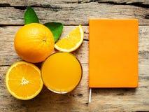 Un vetro di succo d'arancia fresco e gruppo di frutti arancio freschi Fotografia Stock Libera da Diritti