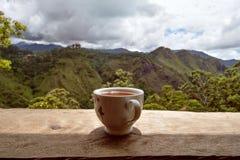 Un vetro di tè caldo sulla tavola nel negozio del tè e la vista sulle piccole dighe alzano nello Sri Lanka Fotografia Stock