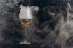 Un vetro di vino bianco su un fondo nero il fumo dal narghilé avvolge il vetro resto, festa primo piano della bevanda alcolica fotografia stock libera da diritti