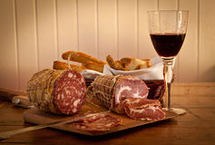 Un vetro di vino con salame e pane casalingo. Fotografie Stock