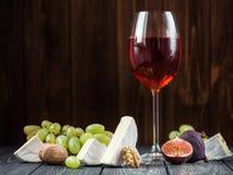 un vetro di vino rosso con gli spuntini Fotografia Stock