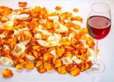 Un vetro di vino rosso e dei petali rosa Fotografia Stock