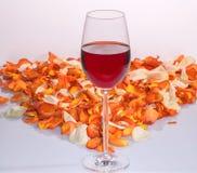 Un vetro di vino rosso e dei petali rosa Immagini Stock Libere da Diritti
