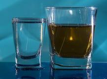 Un vetro di vodka e un vetro di brandy, di whiskey o di bourbon su un bianco o su un fondo colorato Fotografie Stock Libere da Diritti
