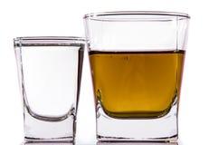 Un vetro di vodka e un vetro di brandy, di whiskey o di bourbon su un bianco o su un fondo colorato Immagine Stock Libera da Diritti