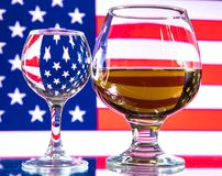 Un vetro di vodka e un vetro di brandy, di whiskey o di bourbon su un bianco o su un fondo colorato Fotografia Stock
